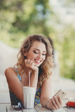 A fun and cheerful model in a summer cafe. Royalty Free Stock Images