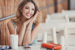 A fun and cheerful model in a summer cafe. Stock Image