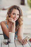 A fun and cheerful model in a summer cafe. Royalty Free Stock Photo