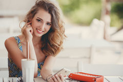 A fun and cheerful model in a summer cafe. Stock Photos