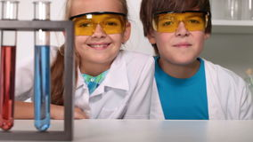 Fun chemistry class - kids giggle in protective glasses stock video