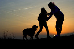 Fun of childen and dog in sunset Stock Photo