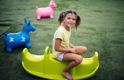 Fun childhood. Smiling girl spending time on playground. Looking at camera. Space for copy royalty free stock photography