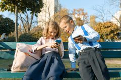 Fun children boy and girl are looking into smartphones. On a bench with school backpacks, background autumn sunny park, golden hou. R stock photos