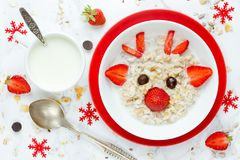 Fun Christmas breakfast idea for kids oatmeal bowl with fruit in Stock Images