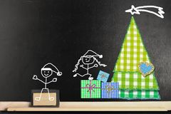 Fun Christmas greeting  card. Fun Christmas card. Funny Christmas card.  Happy boy and girl stickman and fabrics Chtistmas tree  on a blackboard with copy space Stock Image