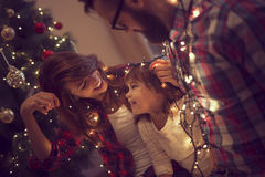 Fun with Christmas lights. Beautiful young family enjoying their holiday time together, decorating Christmas tree, arranging the christmas lights and having fun Stock Images