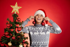 Fun by Christmas tree. Portrait of happy girl in Santa cap trying on red decorative toy balls with xmas firtree near by royalty free stock image