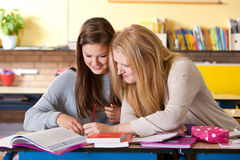 Fun in class. Two teenage girls in the classroom checking the books together Stock Photo