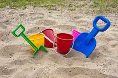 Fun Colorful Children Beach Toys and Sand. Colorful fun toys for children when going to the beach and playing in sand. The colors are red, green blue, yellow Stock Photo