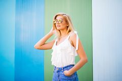 Fun and colorful. Young pretty happy woman in shorts posing against color wall. Young pretty happy woman in shorts posing against color wall Stock Photo