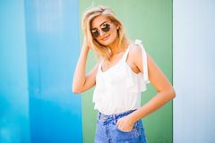 Fun and colorful. Young pretty happy woman in shorts posing against color wall. Young pretty happy woman in shorts posing against color wall Stock Image