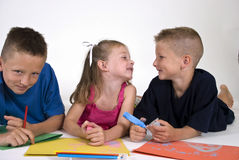 Fun with Coloring. Three happy children lying on the floor coloring on bright colored paper Royalty Free Stock Images