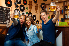 Fun company of two boys and one girl drink in bar Stock Photos