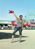 Fun at Coney Island New York USA. Native and African American Brooklyn woman takes off her shoes to walk in the sand at Coney Island NYC stock photos