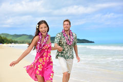 Fun couple on beach vacations in Hawaiian clothing. Happy couple having fun running on Hawaii beach vacations in Hawaiian clothing wearing Aloha shirt and pink royalty free stock photography