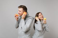 Fun couple girl guy in gray sweaters, scarves together hold orange lemon isolated on grey wall background studio. Portrait. Healthy lifestyle ill sick treatment stock photography