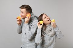 Fun couple girl guy in gray sweaters, scarves together hold orange lemon isolated on grey wall background studio. Portrait. Healthy lifestyle ill sick treatment royalty free stock image