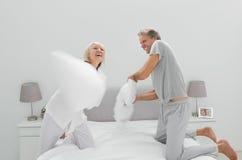 Fun couple having a pillow fight stock photo
