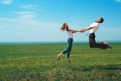 Fun couple in jump on the field Stock Photo