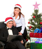 Fun couple looking into laptop near  Christmas tree Stock Photos