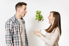 Fun couple man woman standing and throwing up salad from glass bowl isolated on white background. Proper nutrition stock photo