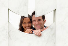 Fun couple peeping through a hole in a sculpture Royalty Free Stock Images