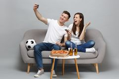 Fun couple woman man football fans cheer up support favorite team doing selfie shot on mobile phone isolated on grey. Fun couple women men football fans cheer up stock images