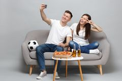 Fun couple woman man football fans cheer up support favorite team, doing selfie shot on mobile phone, showing victory stock image
