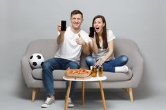 Fun couple woman man football fans cheer up support favorite team holding mobile phone with blank empty screen isolated. Fun couple women men football fans cheer royalty free stock photo