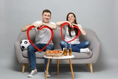 Fun couple woman man football fans cheer up support favorite team, sitting and holding big red wooden hearts isolated on. Fun couple women men football fans stock images