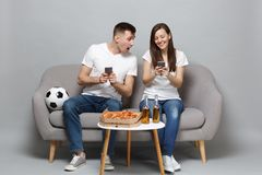 Fun couple woman man football fans cheer up support favorite team sitting holding using mobile phone isolated on grey. Fun couple women men football fans cheer stock image
