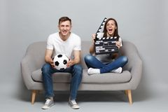 Fun couple woman man football fans cheer up support favorite team with soccer ball hold classic black film making royalty free stock images
