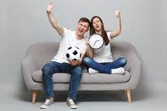 Fun couple woman man football fans cheer up support favorite team with soccer ball, holding round clock, showing thumbs royalty free stock photo