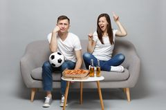 Fun couple woman man football fans cheer up support favorite team with soccer ball, pointing index fingers up isolated. Fun couple women men football fans cheer stock photo