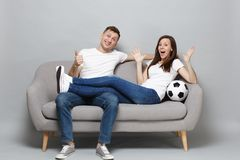 Fun couple woman man football fans cheer up support favorite team with soccer ball spreading hands showing thumb up. Fun couple women men football fans cheer up royalty free stock photo