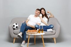 Fun couple woman man football fans in white t-shirt cheer up support favorite team with pipe sitting isolated on grey. Fun couple women men football fans in stock photo