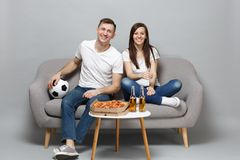 Fun couple woman man football fans in white t-shirt cheer up support favorite team with soccer ball isolated on grey. Fun couple women men football fans in white stock photo