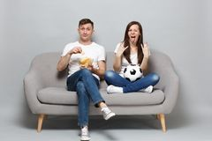 Fun couple woman man football fans cheer up support favorite team with soccer ball, hold glass bowl of chips, depicting royalty free stock image