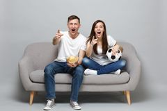 Fun couple woman man football fans cheer up support favorite team with soccer ball hold glass bowl of chips, pointing royalty free stock images