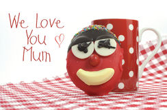 Fun cute childrens handmade cookie with candy face and red polka dot cup of tea or coffee for Mothers Day Royalty Free Stock Photos
