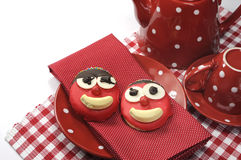Fun cute childrens handmade cookie with candy face and red polka dot cup of tea or coffee Royalty Free Stock Photos