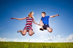 Fun cute couple in jump on the outdoor background Royalty Free Stock Photo
