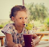 Fun cute thinking kid girl drinking smoothie juice with serious look in summer cafe. Closeup stock photography