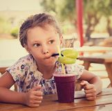 Fun cute thinking kid girl drinking smoothie juice with serious look in summer cafe. Closeup stock photos