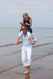 Fun with dad. Cute young girl sitting on dad's shoulders playing in the surf Stock Image