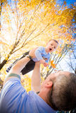 Fun With Dad. A baby boy having fun playing with his dad outside. The boy is being lifted in the air by his father royalty free stock photos