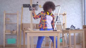 Fun dancing african woman with an afro hairstyle works on wood in the workshop stock video