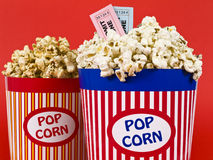 Fun dating. Two popcorn buckets over a red background. Movie stubs sitting over the popcorn Stock Photo