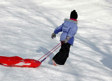 A fun day in the snow. Girl in colorful ski clothing dragging a sled in the snow Stock Image
